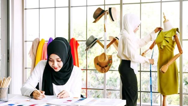 Piękna muzułmańska kobieta kreśli odzieżową sylwetkę przy biurem.