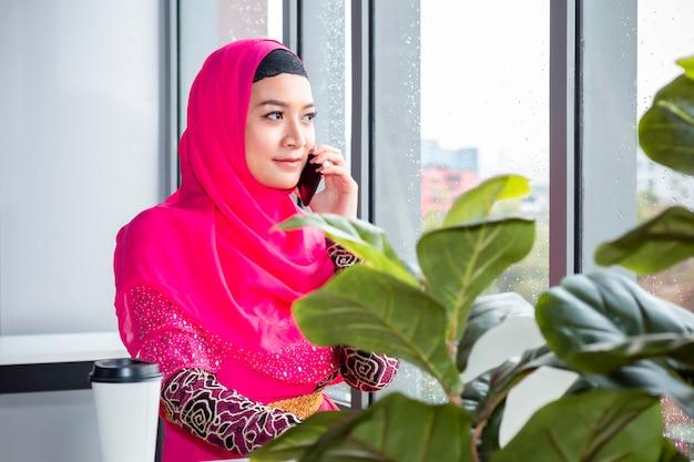 Piękna muzułmańska kobieta opowiada z telefonem na sklep z kawą.