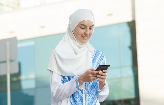 Piękna muzułmańska kobieta texting na telefonie komórkowym outdoors.