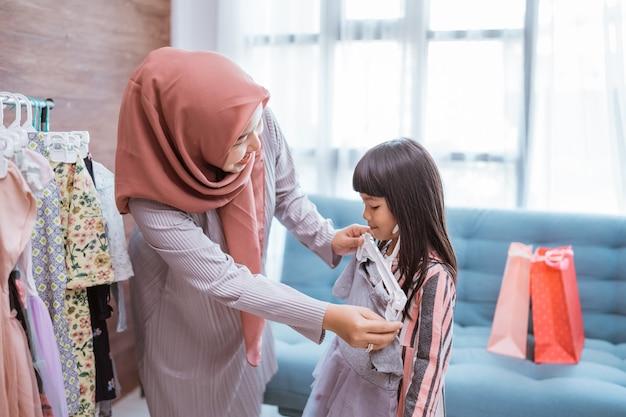 Piękna muzułmańska mama robi zakupy z córką w butikowym sklepie odzieżowym lub zbierając ubrania w szafie