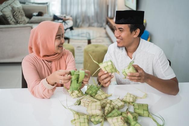 Piękna muzułmańska para azjatycka robi ciasto ryżowe ketupat w domu przy użyciu liści palmowych