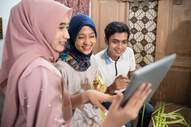 Piękna muzułmańska rodzina i przyjaciel robiący ciasto ryżowe ketupat w domu za pomocą liści palmowych dla tradycji eid fitr mubarak