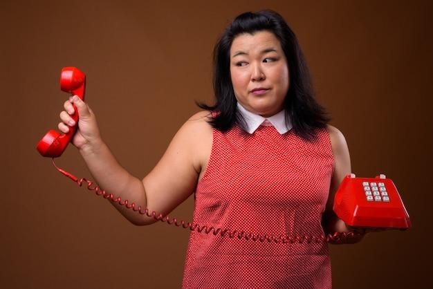 Piękna nadwaga asian kobieta ubrana w czerwoną sukienkę