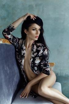 Piękna naga kobieta o długich czarnych włosach siedzi na krześle. idealne ciało gładka czysta skóra i długie nogi. kobieta czeka na ukochanego wieczorem na krześle
