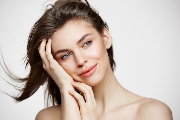Piękna naga młoda kobieta z idealnie czystą skórą, uśmiechając się, dotykając włosów na białej ścianie. zabieg na twarz.