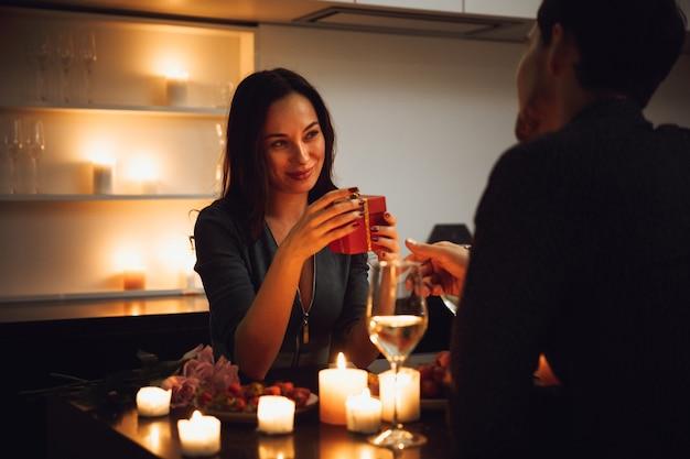 Piękna namiętna para na romantycznej kolacji przy świecach w domu, pijąc wino, kobieta dostaje pudełko