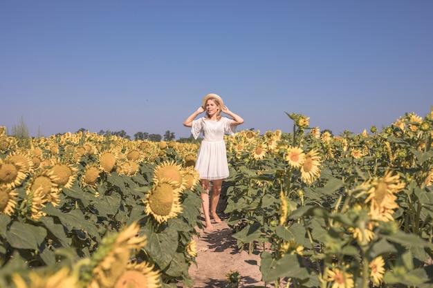 Piękna nasłoneczniona kobieta na żółtym polu słonecznika pojęcie wolności i szczęścia szczęśliwa dziewczyna na zewnątrz