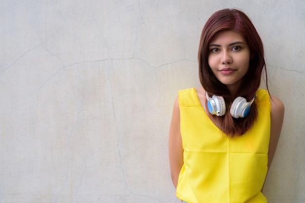Piękna nastolatek dziewczyna jest ubranym żywą żółtą koszula