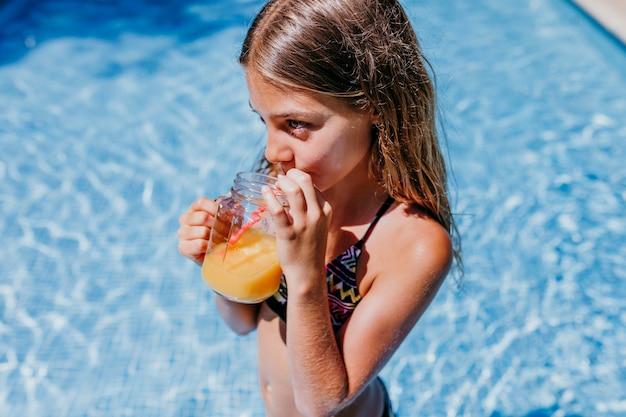 Piękna nastolatek dziewczyna przy basenem pije zdrowego sok pomarańczowego i ma zabawę na zewnątrz. koncepcja czasu letniego i stylu życia