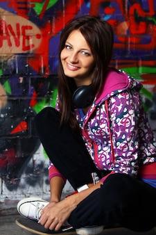 Piękna nastolatek dziewczyna siedzi na deskorolka z hełmofonami