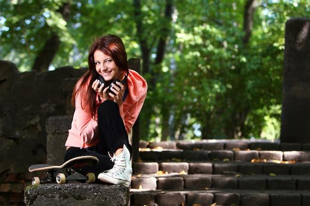 Piękna nastolatek dziewczyna z hełmofonami w parku