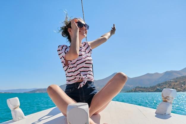 Piękna nastolatka cieszy się letnią wycieczką morską, kobieta siedzi na przedniej części małej łodzi wycieczkowej