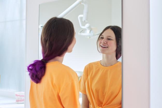 Piękna nastolatka dziewczyna patrząc na białe zdrowe zęby w lustrze w gabinecie dentysty