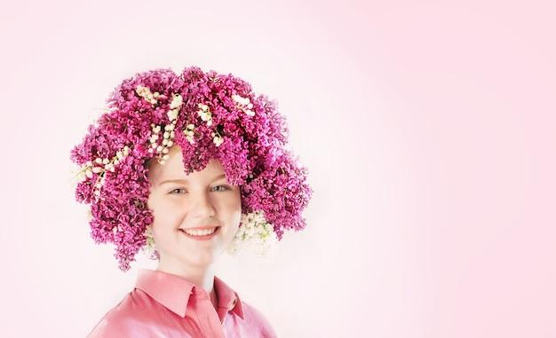 Piękna nastolatka dziewczyna z fryzurą ilac i lily of valey na różowej ścianie