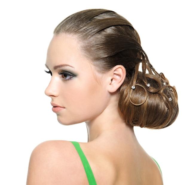 Piękna nastolatka dziewczyna z nowoczesną fryzurę, na białym tle. portret profilowy