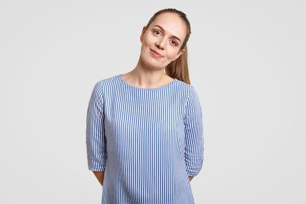 Piękna nastolatka ma ciemne włosy czesane w koński ogon, nosi niebieską koszulę w paski, trzyma ręce za plecami