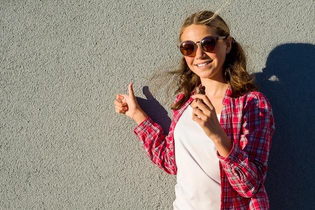 Piękna nastolatka modelu dziewczyna trzyma tabliczkę czekolady i pokazuje kciuk w górę