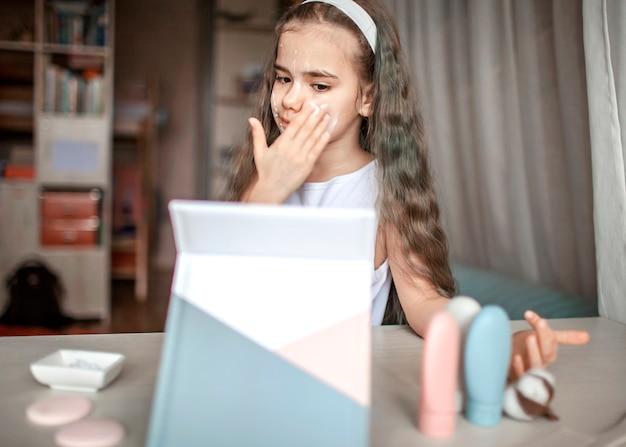 Piękna nastolatka ogląda mistrzowską lekcję urody z tabletem online i sama wykonuje zabieg spa, dziecko z gładką maską na twarzy, salon kosmetyczny w domu