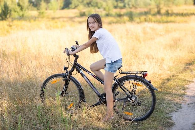 Piękna nastolatka pozuje na rowerze w polu w gorący słoneczny dzień