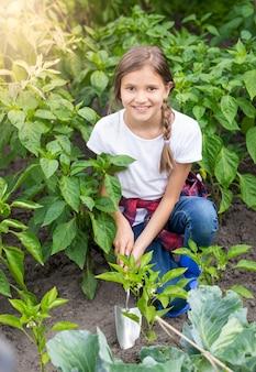 Piękna nastolatka pracująca w ogrodzie z ręczną łopatą
