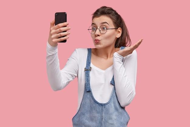 Piękna nastolatka robi grymas, dąsa usta, trzyma telefon przed twarzą