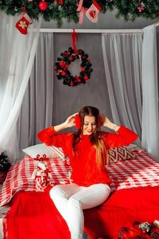 Piękna nastolatka słuchająca muzyki w czerwonych słuchawkach na tle bożego narodzenia