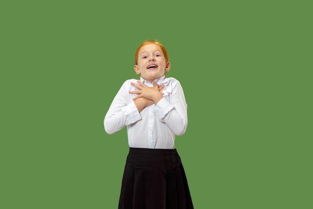Piękna nastolatka szuka zaskoczony na białym tle na zielono