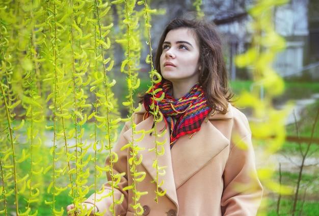 Piękna nastolatka, ubrana w modny oversize'owy beżowy płaszcz i kolorowy szalik, stoi w wiosennym parku