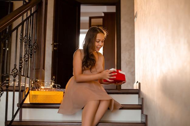 Piękna nastolatka w stroju wieczorowym siedzi w domu