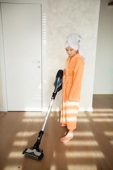 Piękna nastolatka w szlafroku robi sprzątanie domu odkurzaczem