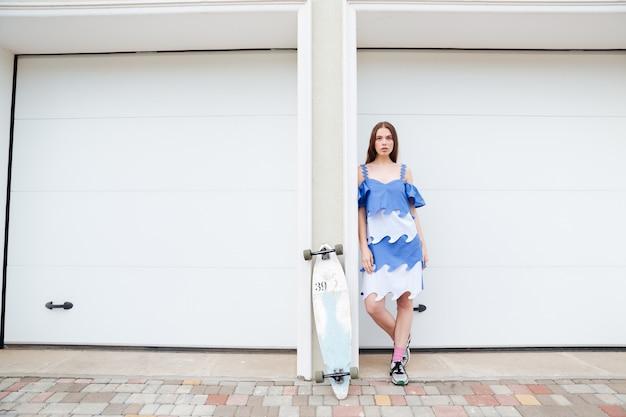 Piękna nastolatka z deskorolką, opierając się na białej ścianie na zewnątrz