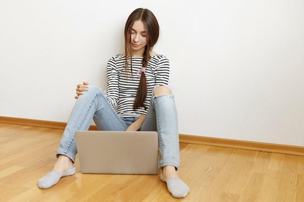 Piękna nastolatka z długimi ciemnymi włosami spoczywa na drewnianej podłodze z typowym laptopem