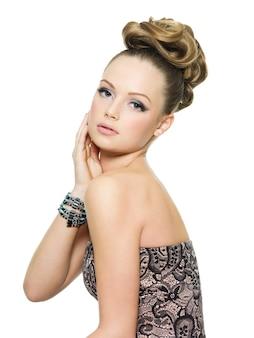 Piękna nastolatka z kręcone fryzury i jasny makijaż na białym tle