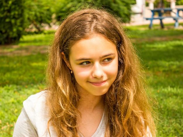 Piękna nastoletnia dziewczyna z długie włosy ono uśmiecha się w parku na zielonej trawie