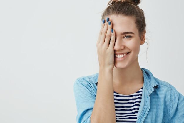Piękna nastoletnia kobieta zakrywa jeden oko z jej ręką