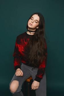 Piękna nastoletnia modelka w stylowej czarno-czerwonej bluzie i czarnym naszyjniku na szyi pozuje na ciemnozielonym tle
