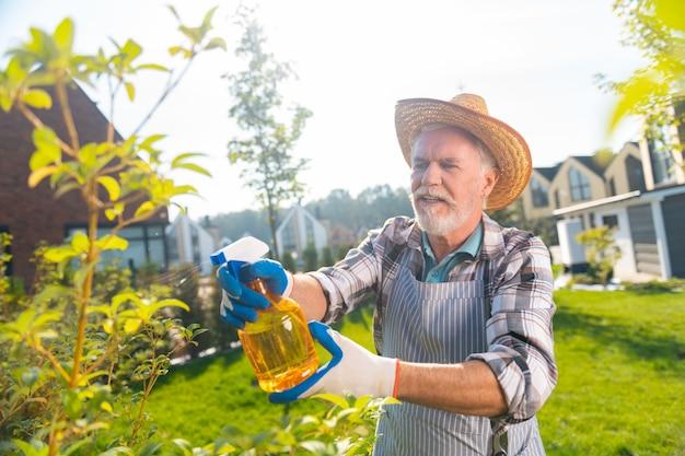 Piękna natura. atrakcyjny sympatyczny emeryt czuje się zmotywowany do pielęgnacji ogrodu