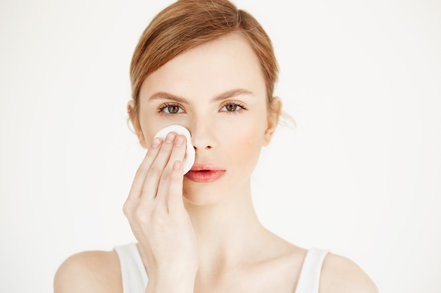 Piękna naturalna blondynki dziewczyny cleaning twarz z bawełnianą gąbką. kosmetologia i spa.