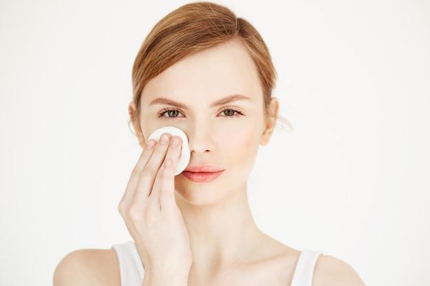 Piękna naturalna blondynki dziewczyny cleaning twarz z bawełnianej gąbki ono uśmiecha się. kosmetologia i spa.