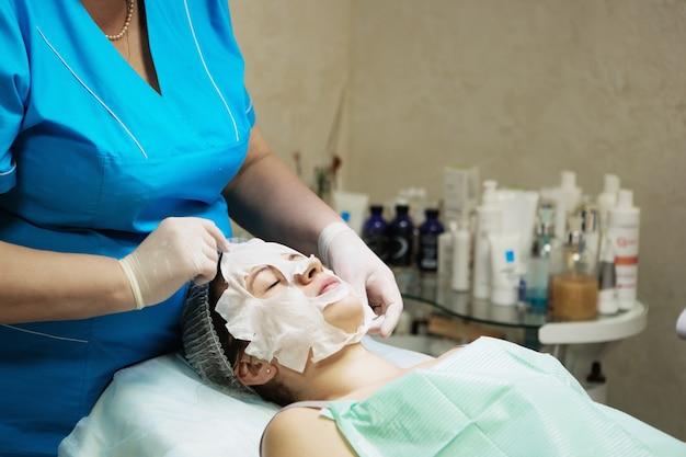 Piękna naturalna dziewczyna kobieta w salonie spa, robi maseczkę na twarz, zabieg odmładzania twarzy, zabiegi spa