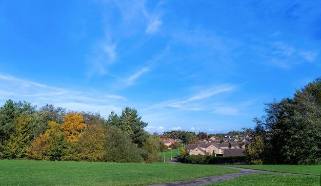 Piękna naturalna łąka krajobrazowa w małej wiosce z błękitnym niebem i może wczesną jesienią.