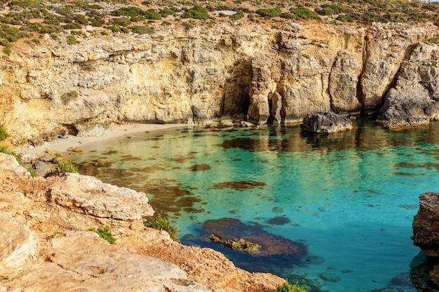 Piękna niebieska laguna z turkusową czystą wodą i wysokim skalistym wybrzeżem żółtego wapienia w słoneczny letni dzień. comino, malta