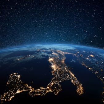 Piękna niebieska planeta ziemia z nocnymi światłami miasta. europa środkowa i włochy w nocy widok z kosmosu. nowoczesne miasta i elektryczność