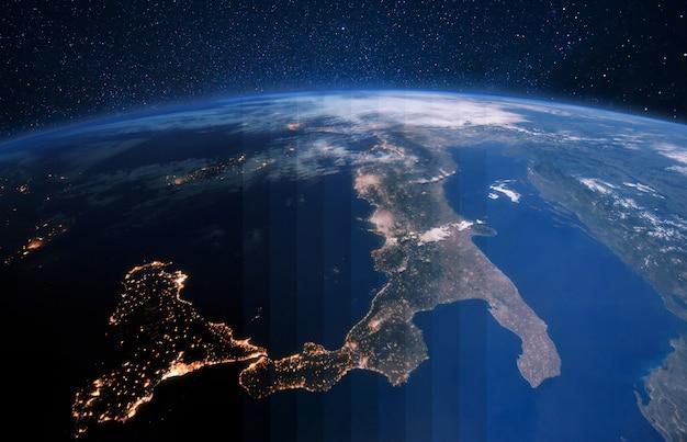 Piękna niebieska planeta ziemia z światłami miasta z kosmosu na rozgwieżdżonym niebie. przejście z nocy na dzień. włochy i europa środkowa z kosmosu