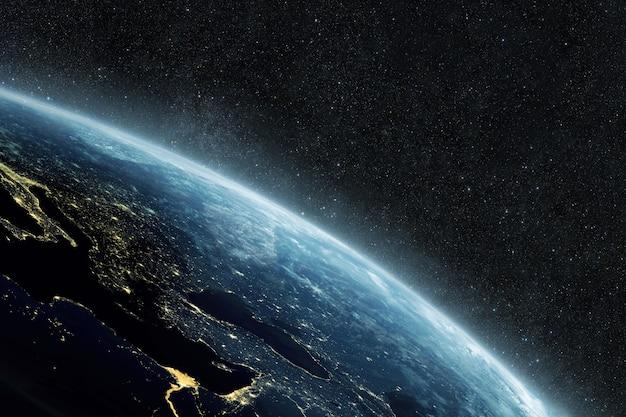 Piękna niebieska planeta ziemia z żółtymi światłami miasta na gwiaździstym tle w kosmosie
