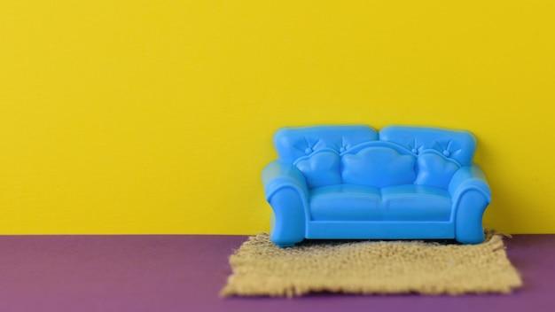 Piękna niebieska sofa z dywanikiem na fioletowej podłodze przy żółtej ścianie. próbka pięknych mebli do domu. minimalistyczny.