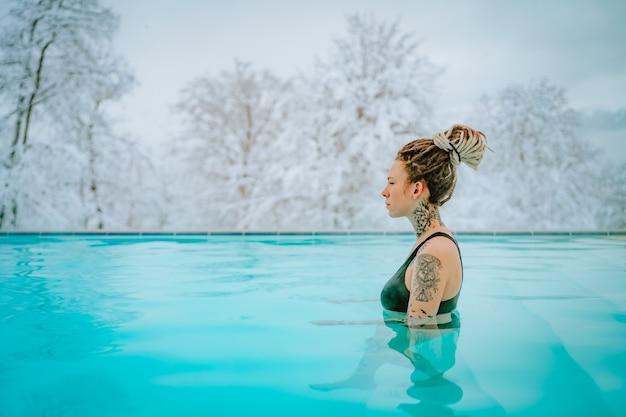 Piękna niebieskooka androgyniczna dziewczyna z dredami i tatuażami w ciepłym basenie