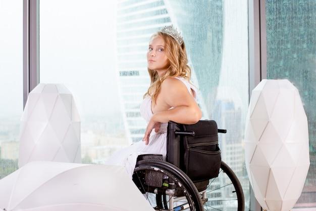 Piękna niepełnosprawna panna młoda pozuje na wózku inwalidzkim na tle panoramicznego okna z widokiem na wieżowce i duże miasto, uśmiecha się do kamery, pojęcie przezwyciężenia niepełnosprawności