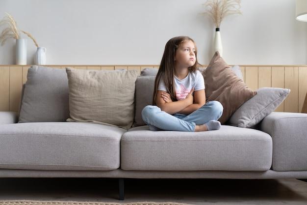 Piękna, nieszczęśliwa, smutna mała 6-letnia dziewczynka siedzi ze skrzyżowanymi nogami na kanapie w salonie, czuje się znudzona i samotna, będąc sama w domu, podczas gdy jej rodzice spędzają cały dzień w pracy