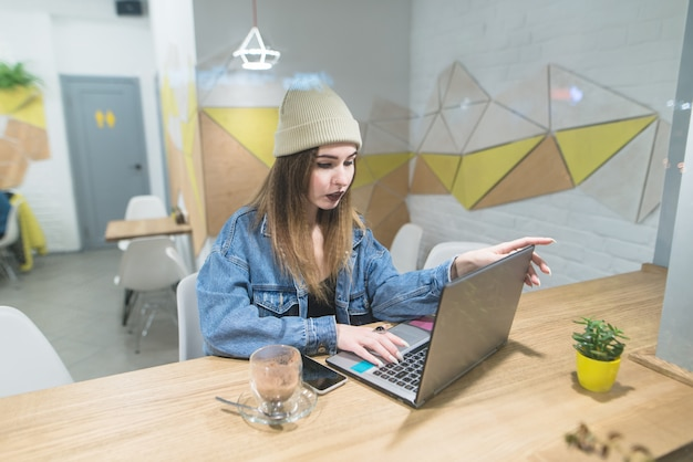 Piękna niezależna dziewczyna pracuje na laptopie w stylowej kawiarni.